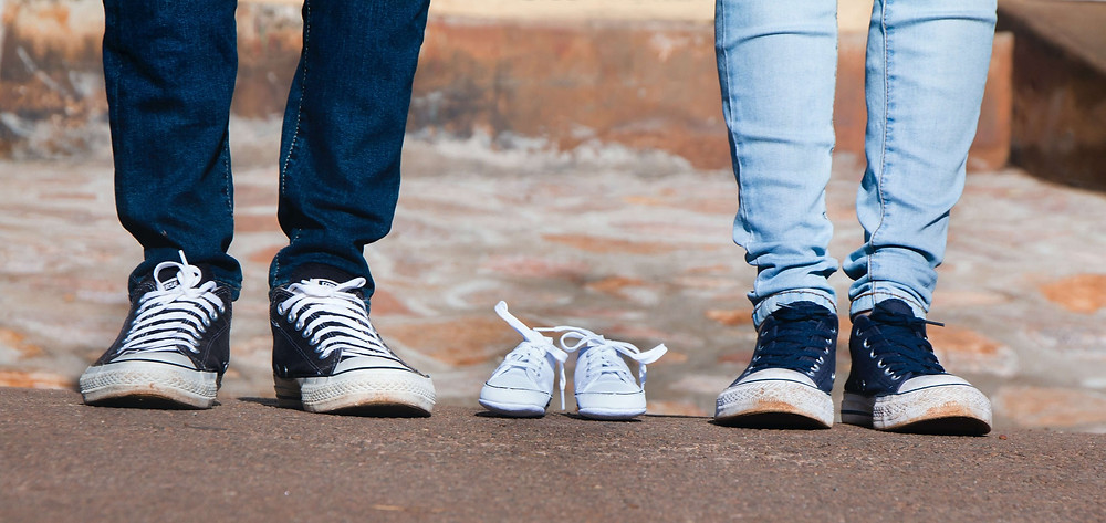 Man and woman wearing converse shoes with baby converse in between announcing pregnancy