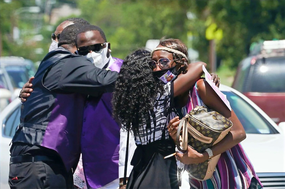 Family members embrace after double funeral for mother and daughter who both died of coronavirus in Dallas on Thursday.