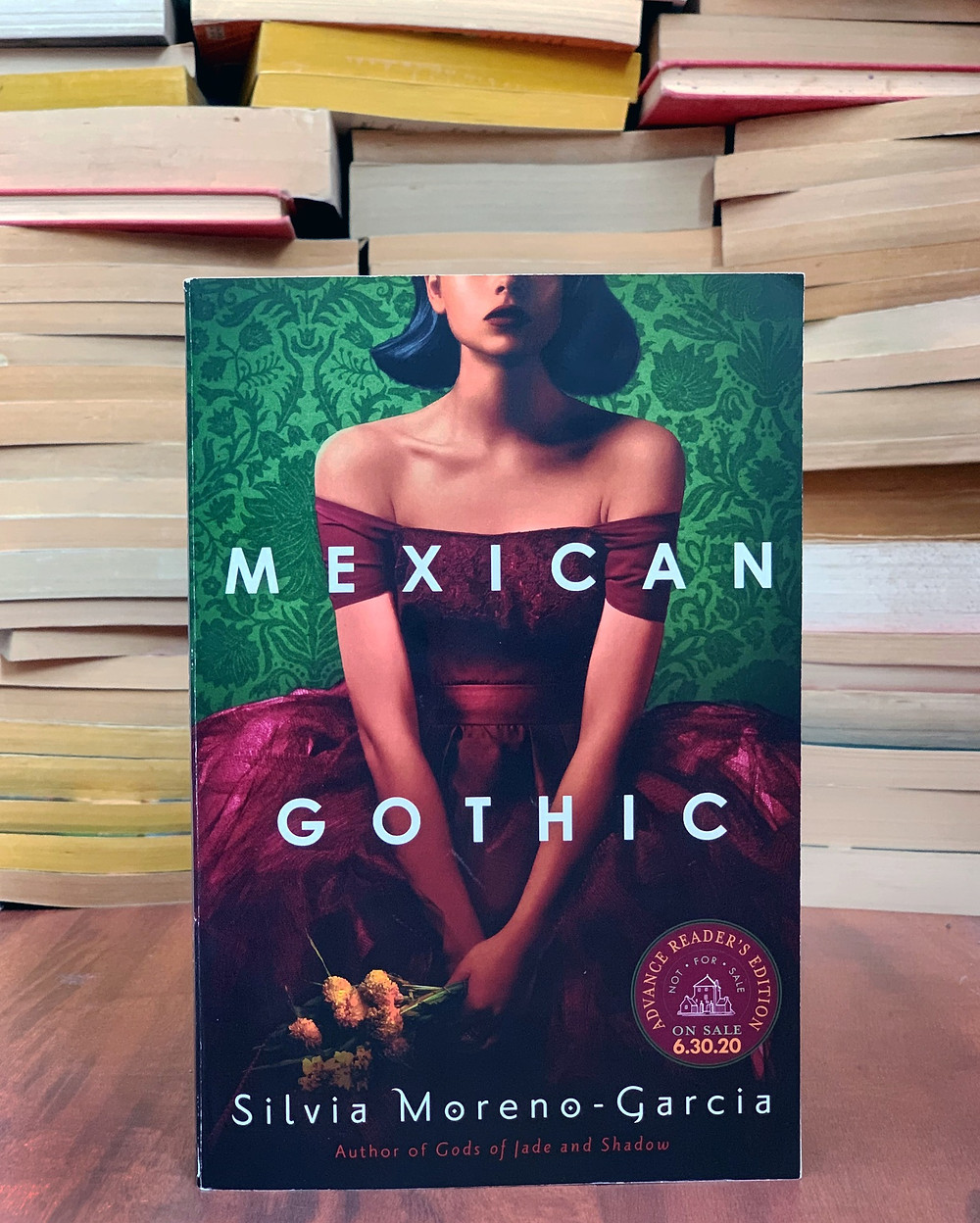 A copy of Mexican Gothic sits in front of a pile of yellowing pages of books