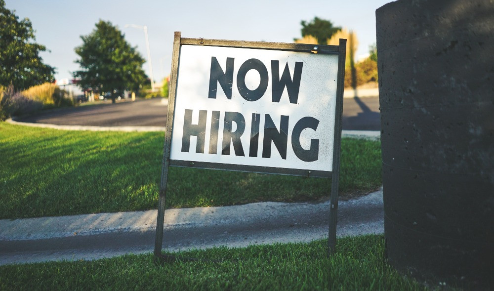 """A sign reads """"NOW HIRING"""" in a patch of grass within a parking lot."""