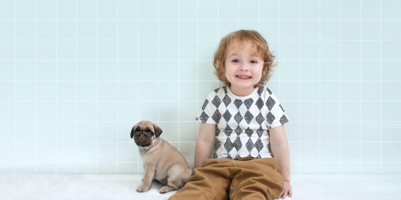 little boy sitting with a cute pug puppy