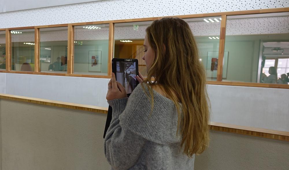 Een foto van een student die een film maakt met een tablet. Deze film wordt gemaakt in de gang van school.