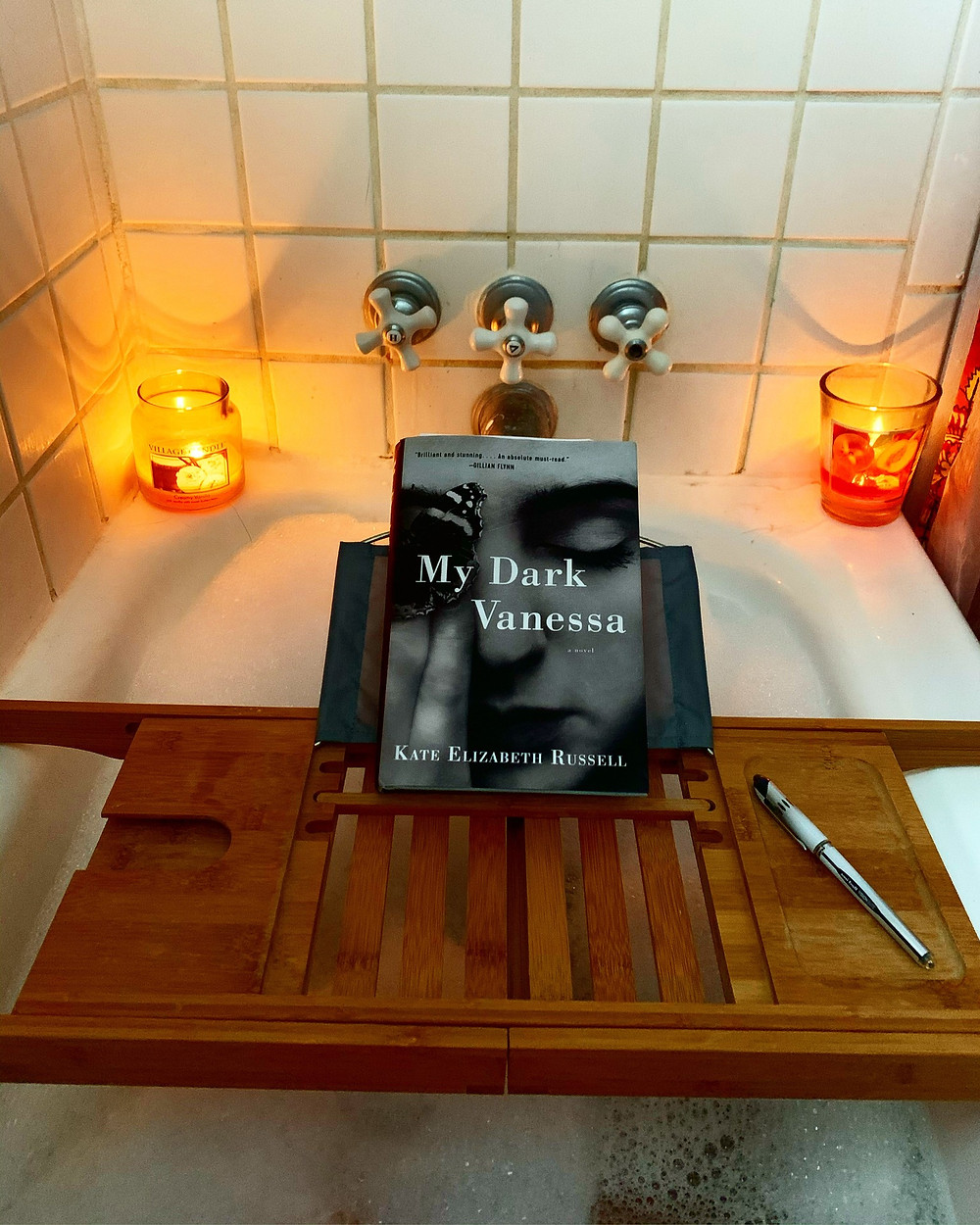 A bathtub filled with suds and adorned by candles with a shelf above with My Dark Vanessa and a pen on it.