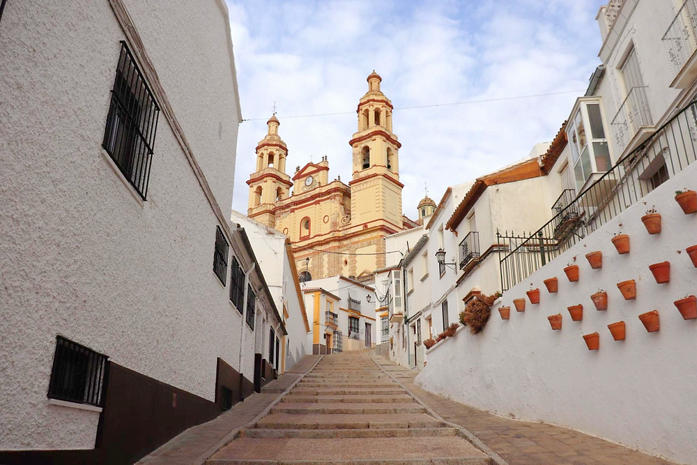 Calle Calzada in Olvera with the church and white buildings along it, Spain