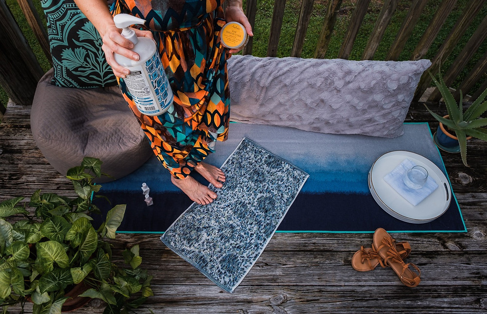 Woman with moisturizers looking down at her feet in a comfortable deck scene, getting ready for a self care DIY manicure and pedicure for personal brand photography.