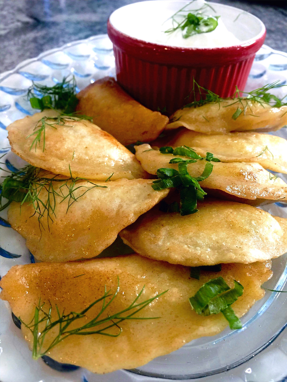 Plate of fried varenki (pierogies) topped with herbs, and a small bowl of sour cream