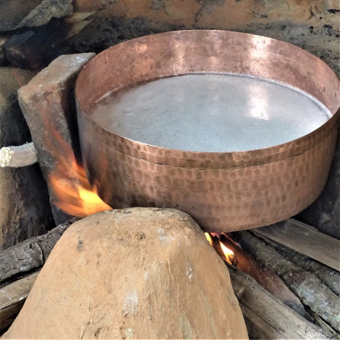 Copper pot with food on the boil on an open fire.