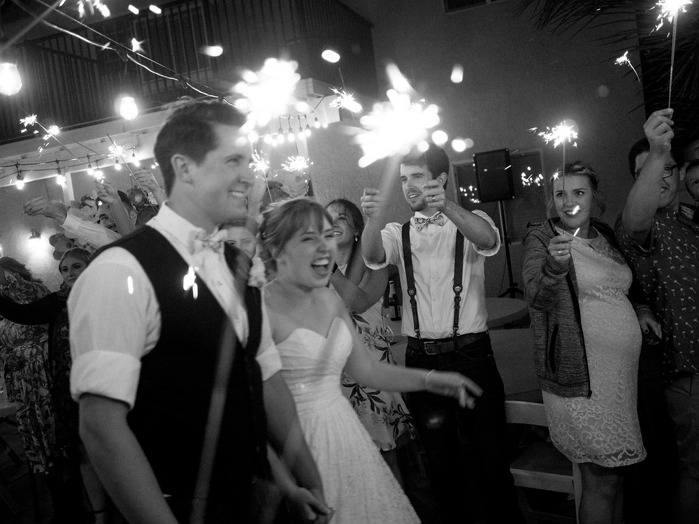 Couple leaving the reception surrounded by family, friends, and sparklers