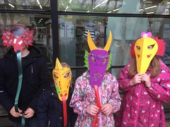 Children wearing dragon masks they made with the help of Penny Sobr