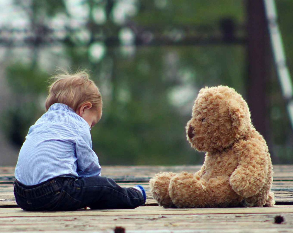 Child sitting with a bear