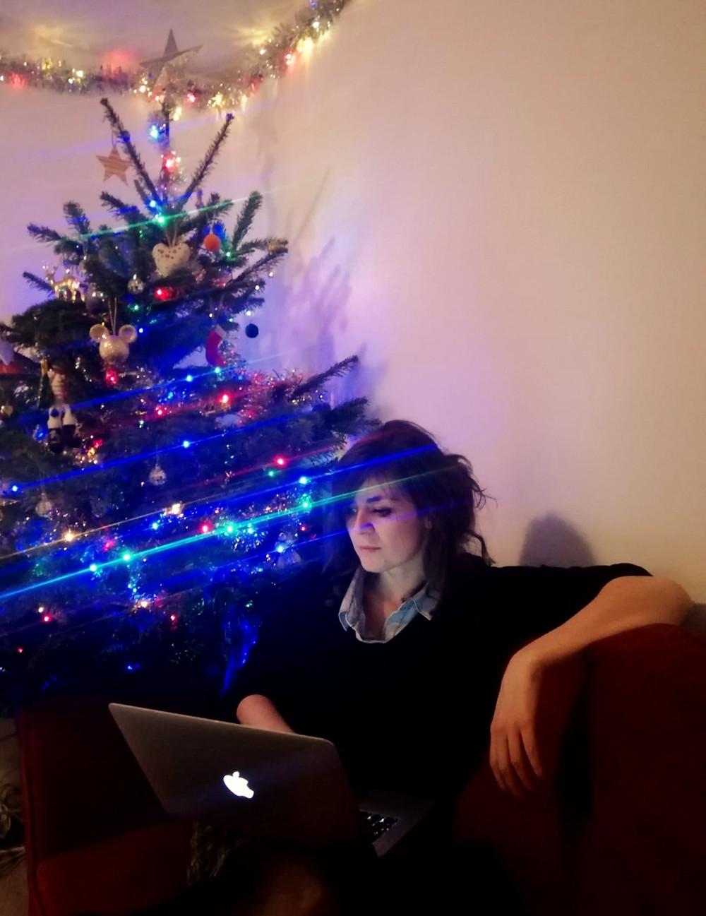 Hannah Duncan Christmas writing, Christmas tree, laptop, young woman, apple computer, on a red sofa, tinsel and lights, copywriter at Christmas