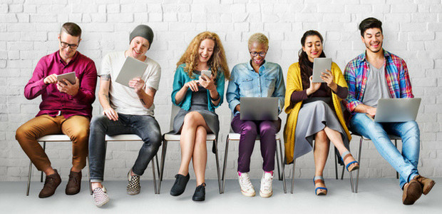 Group of young adults browsing social media on mobile devices - increase organic Facebook reach at TotalCom Marketing in Tuscaloosa, AL