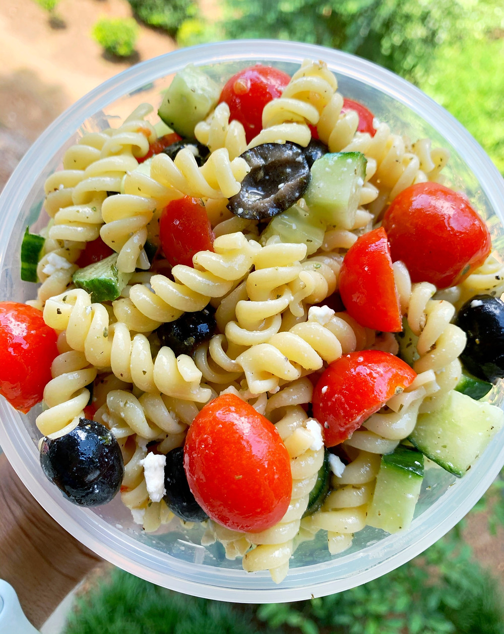 overhead shot of pasta salad with rotini pasta, cherry tomatoes, black olives, cucumber, and feta