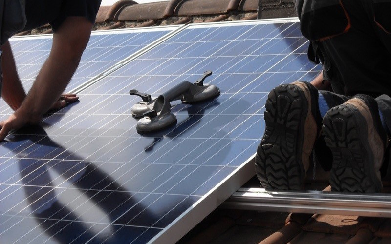 People working maintenance on solar panels