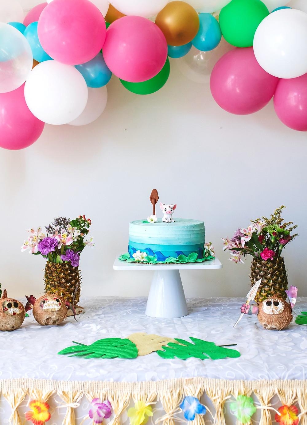 A Moana birthday party table set up with a moana themed cake and a Hawaiian balloon garland.