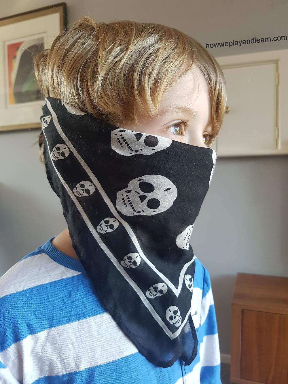 Child playing corona facemask with bandana