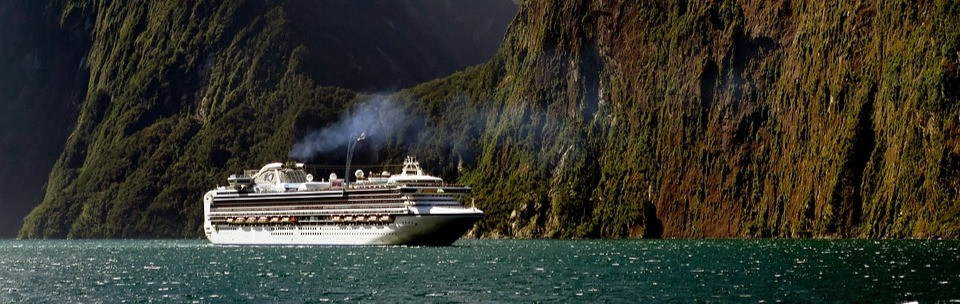 White cruise boat on water surrounded by mountains