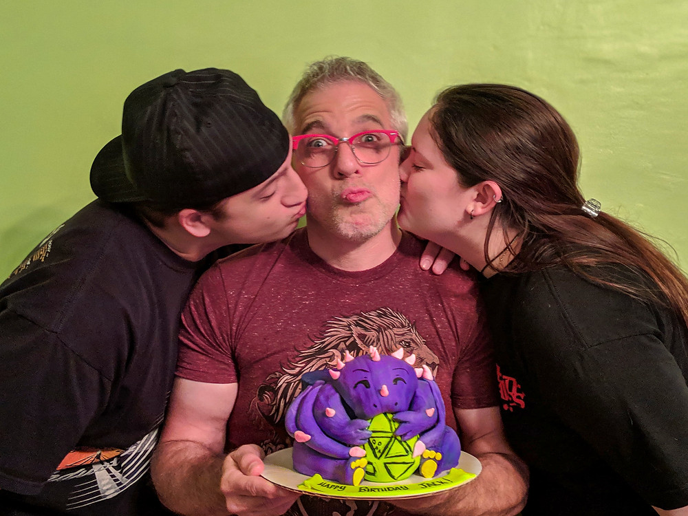 Joey and Jess on either side of Jack, kissing his cheek. Jack is holding a DOTS Dragon cake
