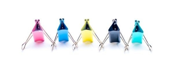 Different colour paperclips joined together. One pink, one blue, one yellow, one black, one aquamarine