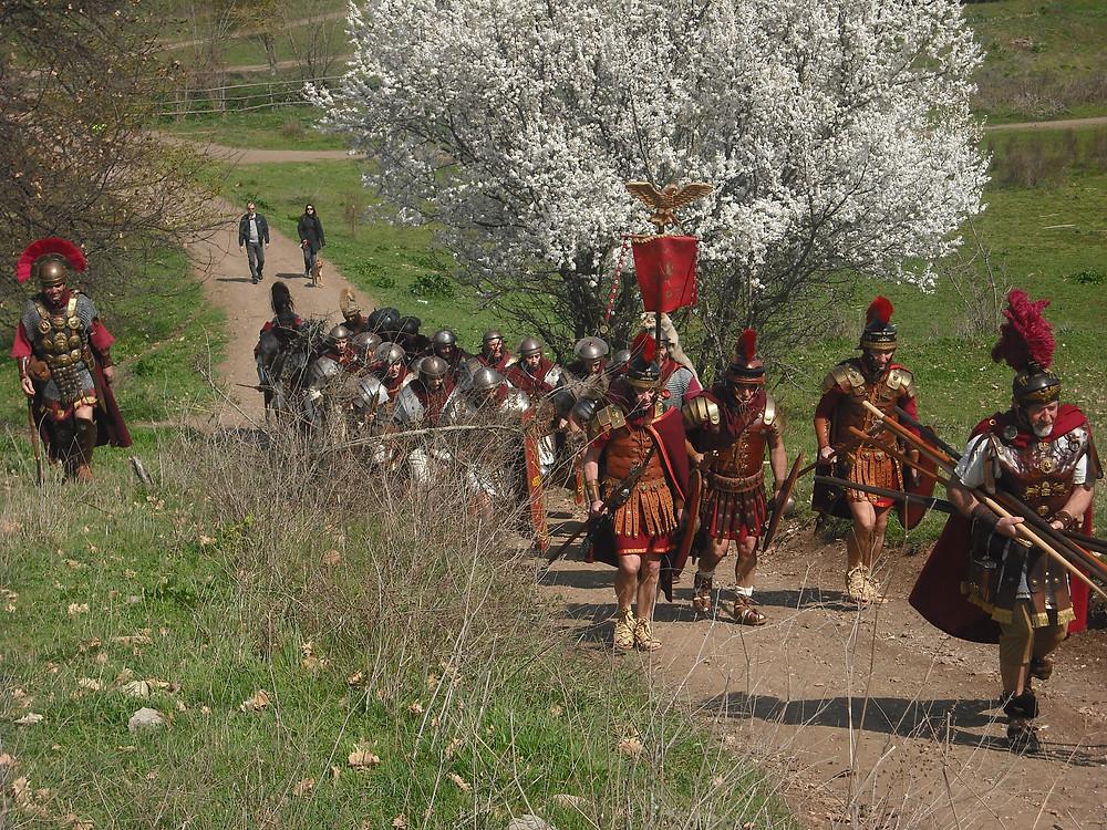 Un grupo de hombres vestidos de legionarios romanos de época imperial hace instrucción por el centro de un camino ascendente. En el fondo a la derecha se aprecia un almendro en flor. Atrás, una pareja pasea un perro.
