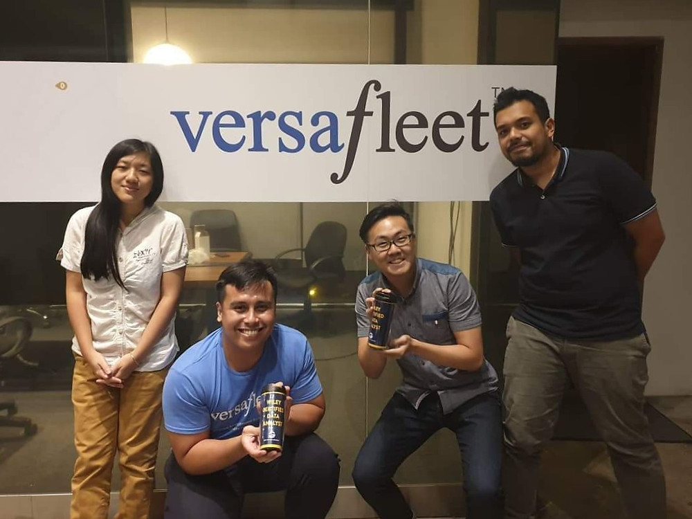 4 people posing for a photo with the Wiley Certified Data Analyst bottle