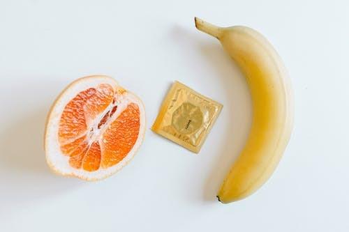 an orange, condom, and a banana