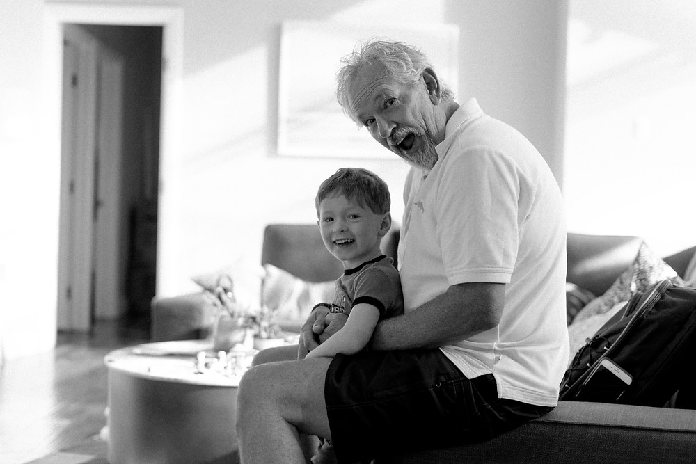 Portrait of a young boy and his grandpa, sitting on the couch and smiling