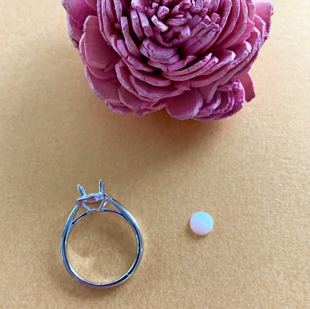 loose round white opal showing play of colour on peach background next to a white gold ring semi mount next to dry pink rose prop