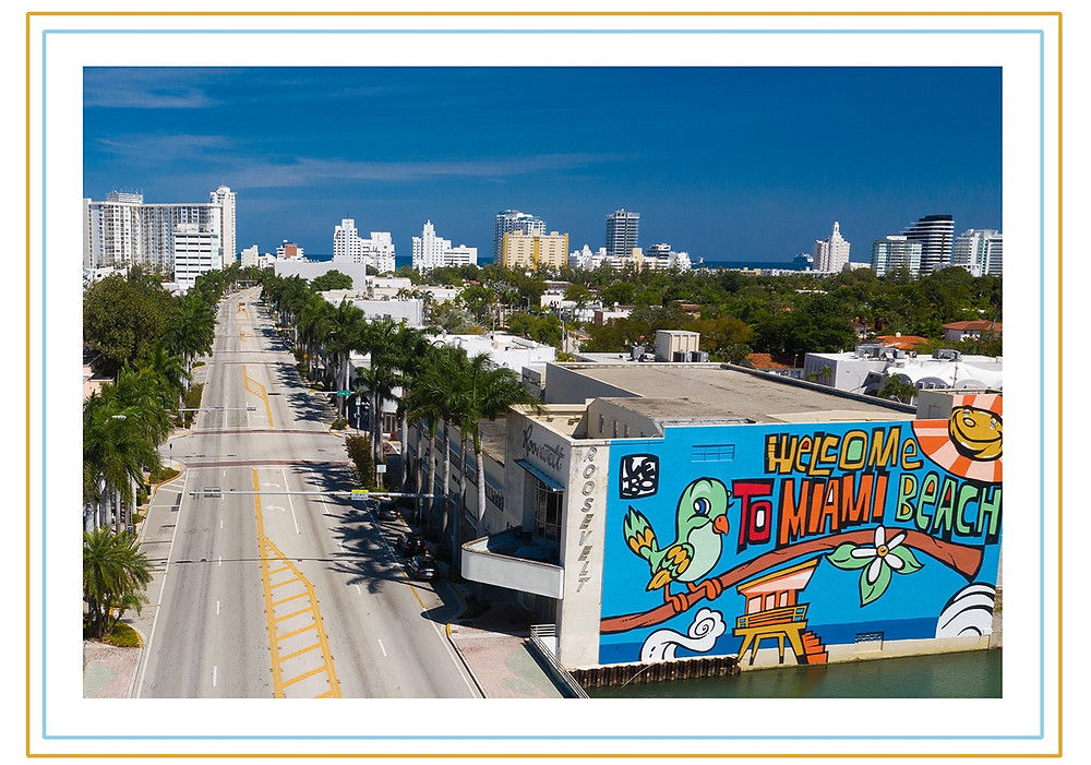 A photograph of colorful mural welcome to Miami Beach, captured on the edge of Arthur Godfrey Road,  just as you enter Miami Beach from Julia Tuttle Causeway. Noticeably absent are vehicles and people going about their daily lives.