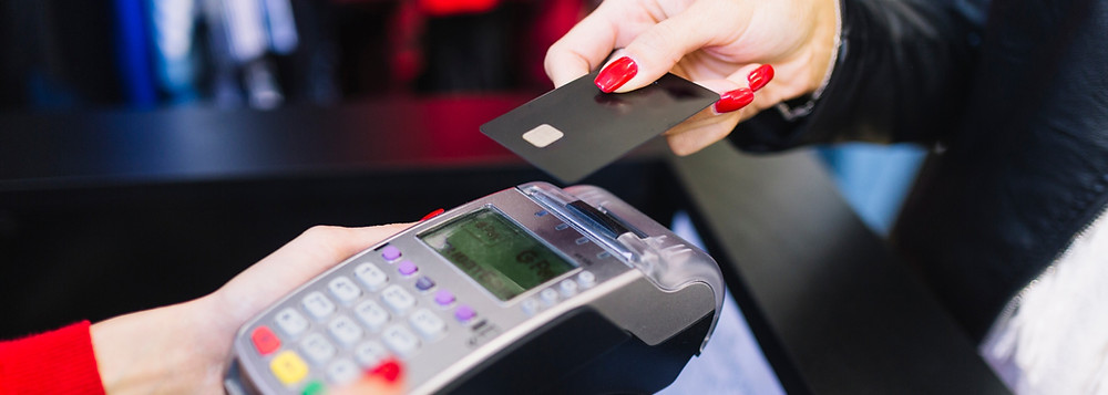 Mão feminina segurando um cartão de crédito próximo a uma maquina de pagamentos.