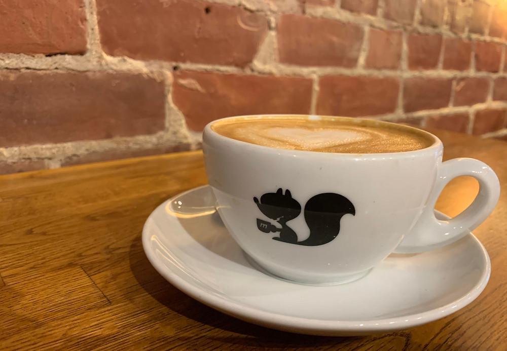 latte in iconic Manic Coffee logo mug with saucer