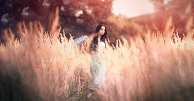 Beautiful, romantic woman in fairytale, wood nymph among tall grass and rays of sun. Outdoor