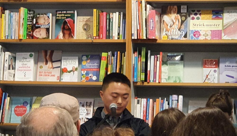 Vor einem Bücherregal Audun Mortensen mit Mikrofon vor Zuschauern