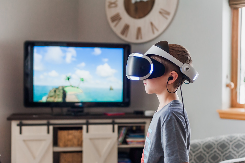 A little boy standing in the front of a TV wearing a VR glasses on his head.
