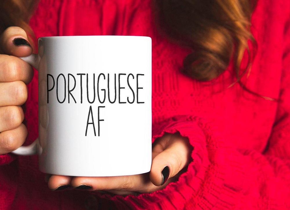 A woman holds a coffee mug that says Portuguese AF