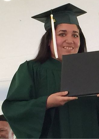 Image of Jasmin, wearing her green graduation cap and gown, posing with her diploma.
