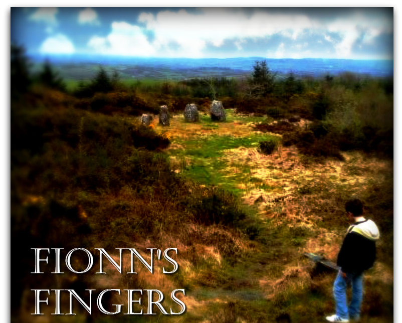 A row of 5 standing stones graduating in size, set in an elevated clearing overlooking rolling countryside.