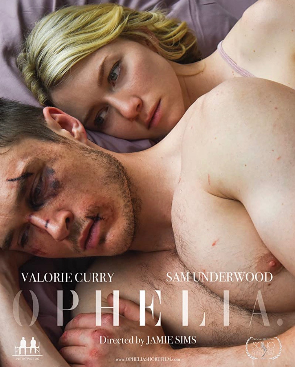 A man and a woman (Ophelia and Hamlet) lay in a bed together, Hamlet's back is turned to face Ophelia as she gazes upon the back of his head. Hamlet's face is badly beaten with bruises and cuts in all areas. The colours are subtle but the overall image is bright with natural light.
