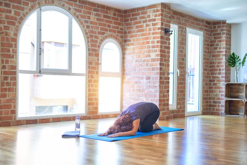 Woman in yoga studio doing child's pose