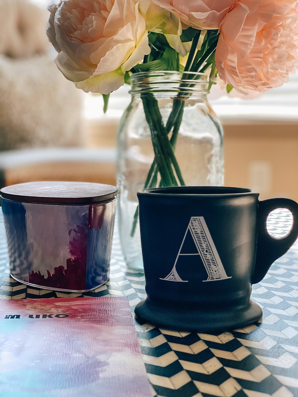 a notebook and coffee cup in front of a candle and bouquet of peonies