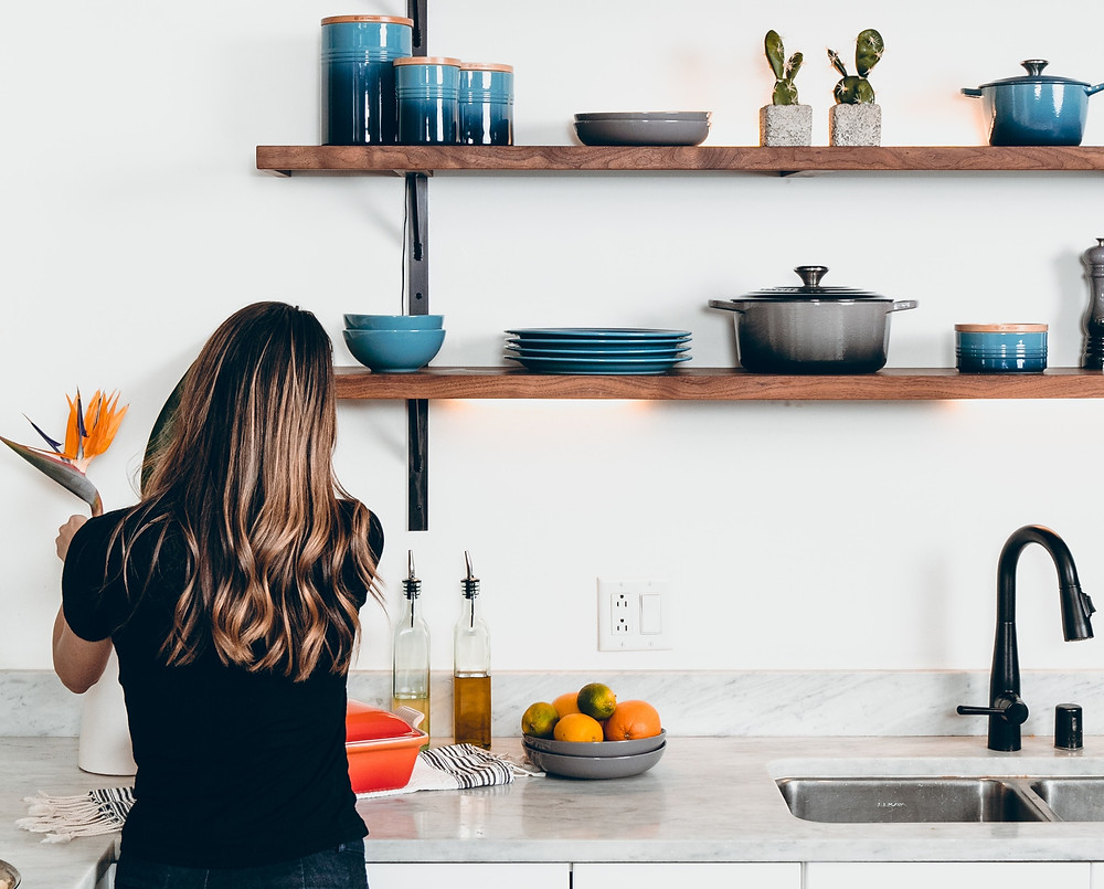Girl making dinner in a clean white kitchen