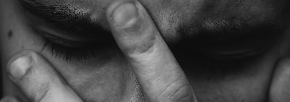 A Black and White picture of a man with his eyes closed and his hand holding, with open fingers his head.  The image is just from his eyebrows to the middle of his nose.