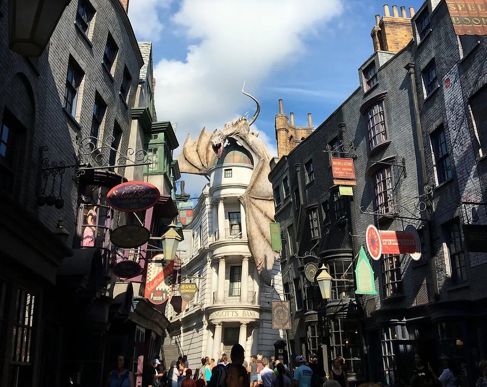 Diagon Alley, with crooked buildings and a view of Gingotts Bank with a dragon perched on top at Universal Studios Florida