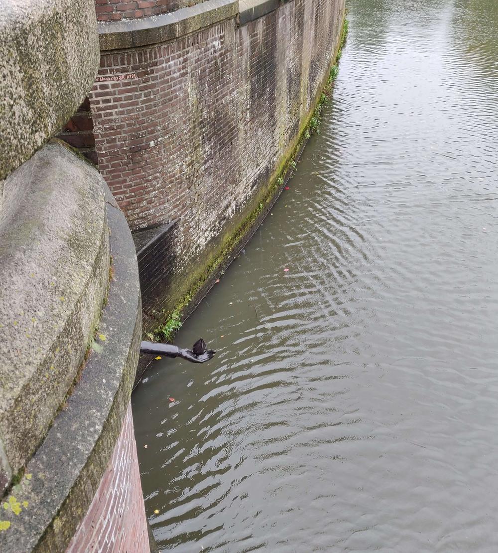 פסלון היד עם הלהבה שיוצאת מקיר הגשר