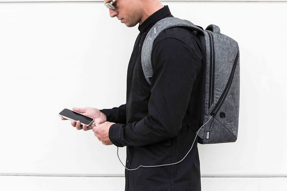 A man conveniently traveling with a suit in his backpack
