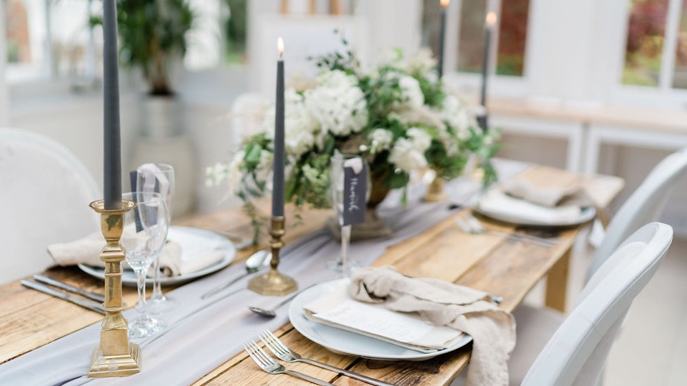 Rustic wooden table with silver runner and brass candlesticks