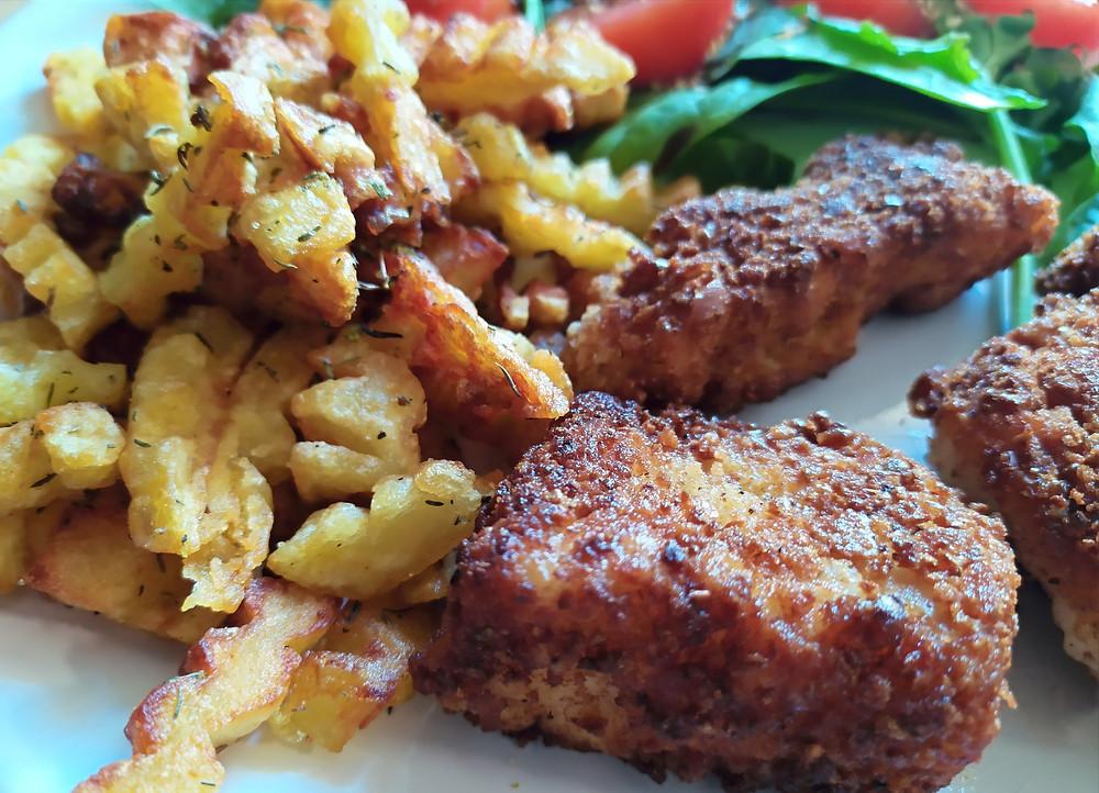 Assiette gros plan cabillaud pané et frites aux herbes
