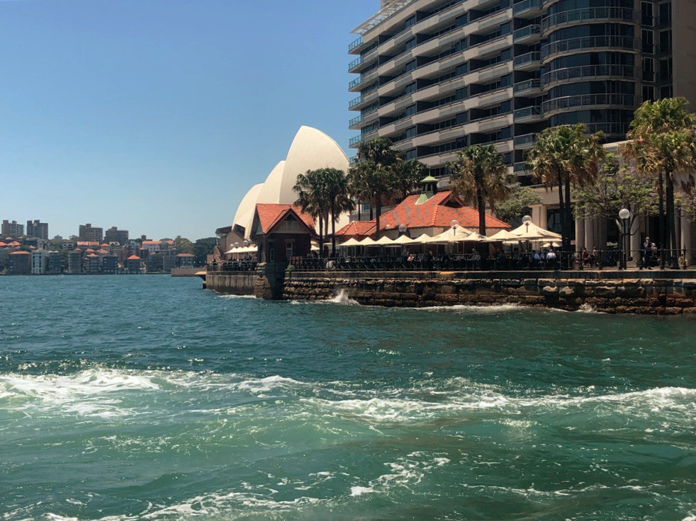 Circular Quay partial view from ferry leaving the harbor showing building, waterside restaurant, Sydney Opera House and city skyline in background