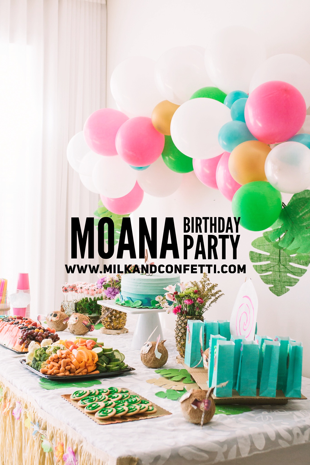 A Moana themed kids birthday party with a balloon garland backdrop, pineapple vases, coconuts and a Moana cake on a party table.