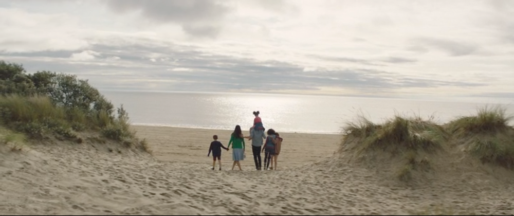 A family walking through sand-dunes in the evening